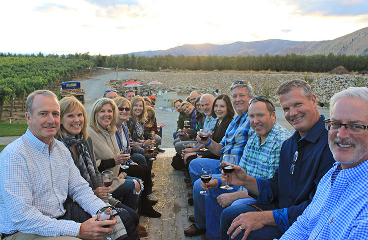 People riding on a vineyard tour with glasses of wine